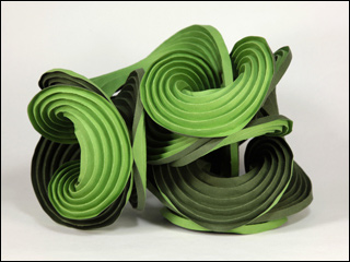 Green paper folded along multiple curved creases to form curved fins of a sculpture.