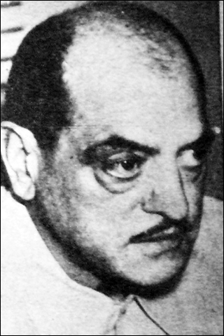 A black and white photograph of a man. He is balding and has a thin mustache.