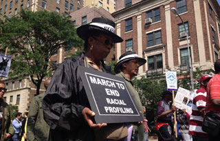 "In the midst of other marchers, a black woman holds a sign reading: ""March to End Racial Profiling."""