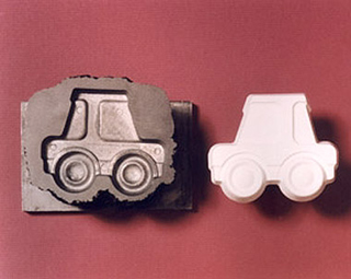 A mold of a toy car and a casting of the car.